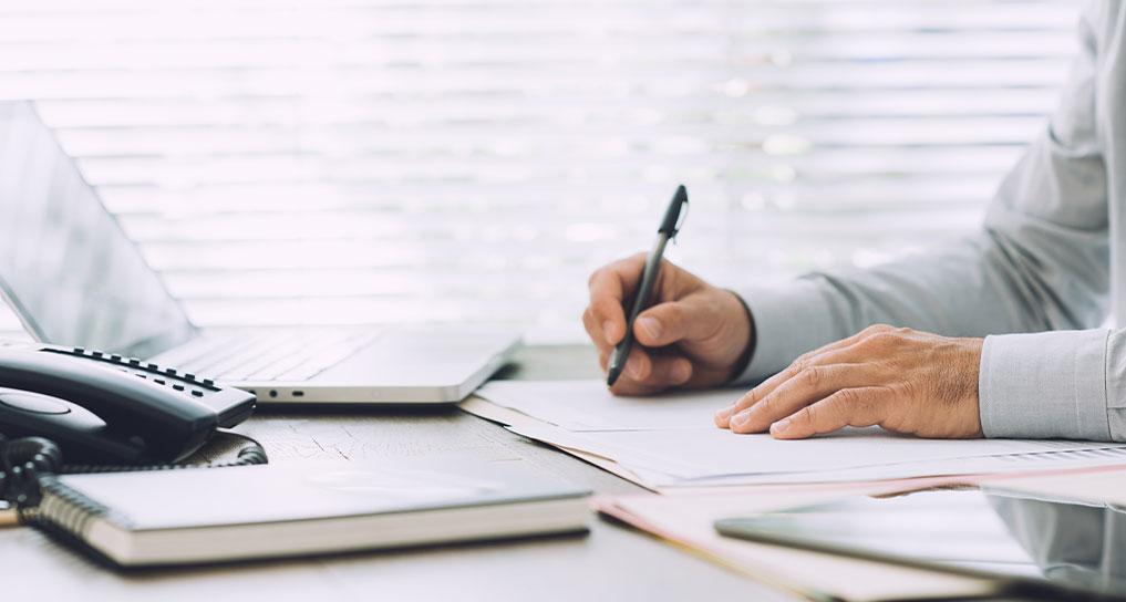 Man bezig met aangifte inkomstenbelasting op papier